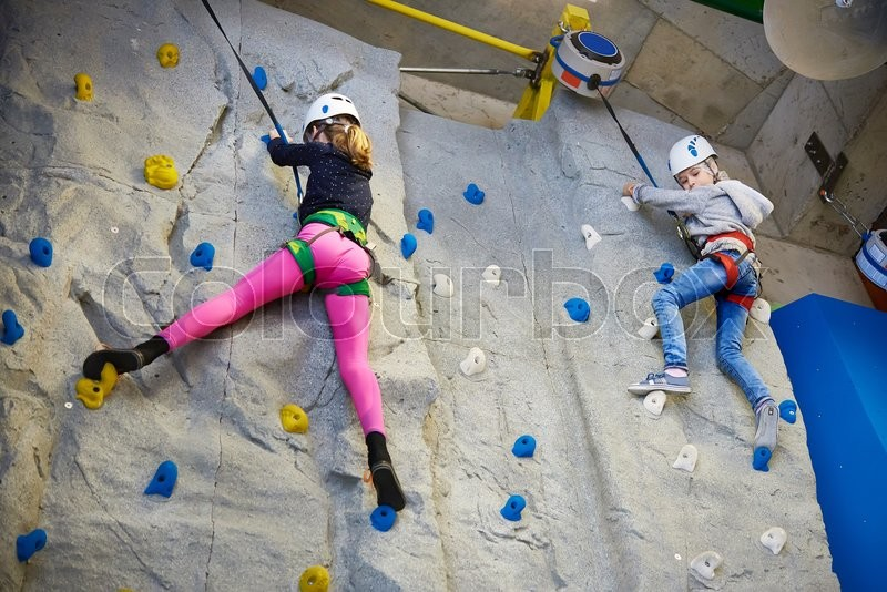 Stock image of 'Two girls climbing to amusement park on blue wall'