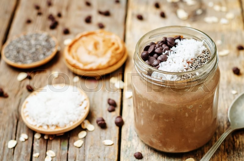 Stock image of 'Chocolate Coconut Chia seeds overnight oats on a dark wooden background. toning. selective focus'
