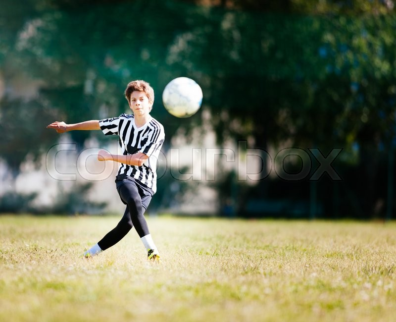 Boy playing football in a soccer field. Caucasian kid dresses a black and white soccer uniform and yellow shoes. Sunny day, stock photo