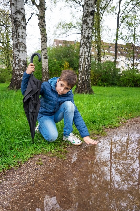 Stock image of 'Outdoor portrait of adorable boy  under the rain'