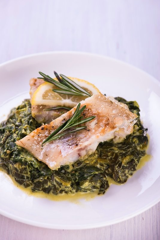 Stock image of 'White fish fillet with herbs on fried spinach'