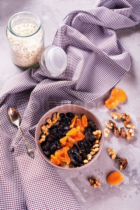 Stock image of 'Oatmeal with raisins, walnuts, dried apricots and plums, cinnamon and honey '