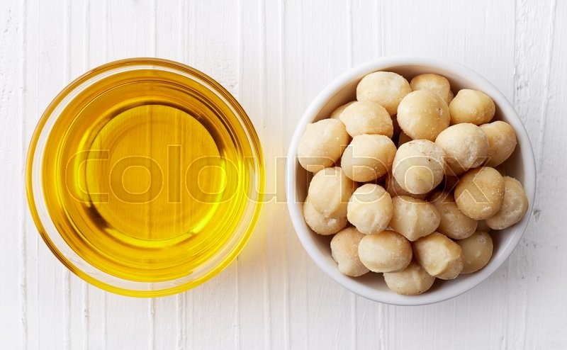 Stock image of 'Macadamia nut oil and macadamia nuts on white wooden background from top view'