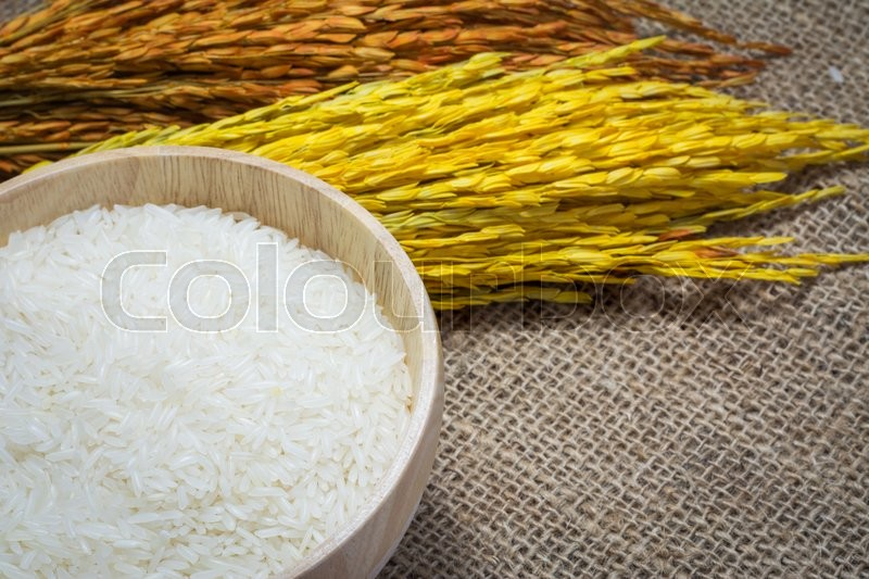 Stock image of 'Rice in wooden bowl on Sack or wood table background'