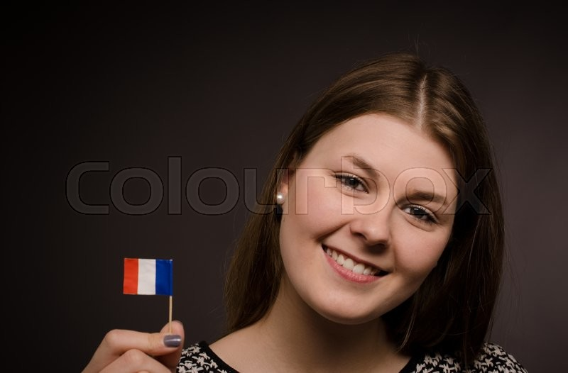Stock image of 'Beautiful smiling woman with a little flag of France'