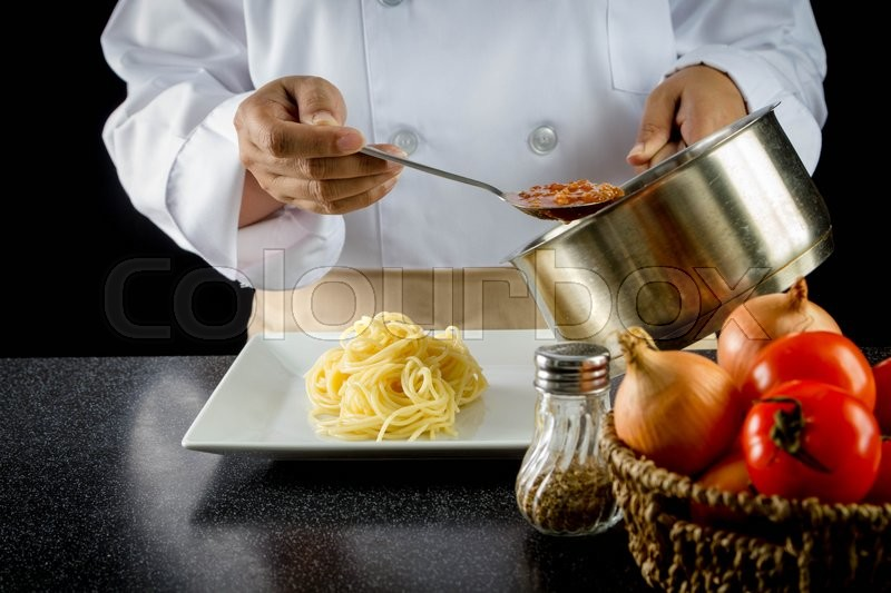 Stock image of 'chef making spaghetti in kitchen at restaurant'