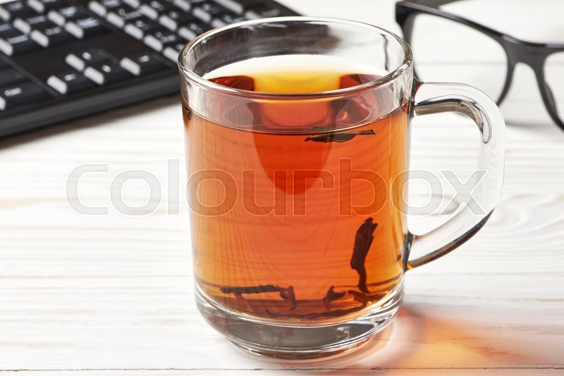 Stock image of 'Cup of tea and keyboard on wooden background'