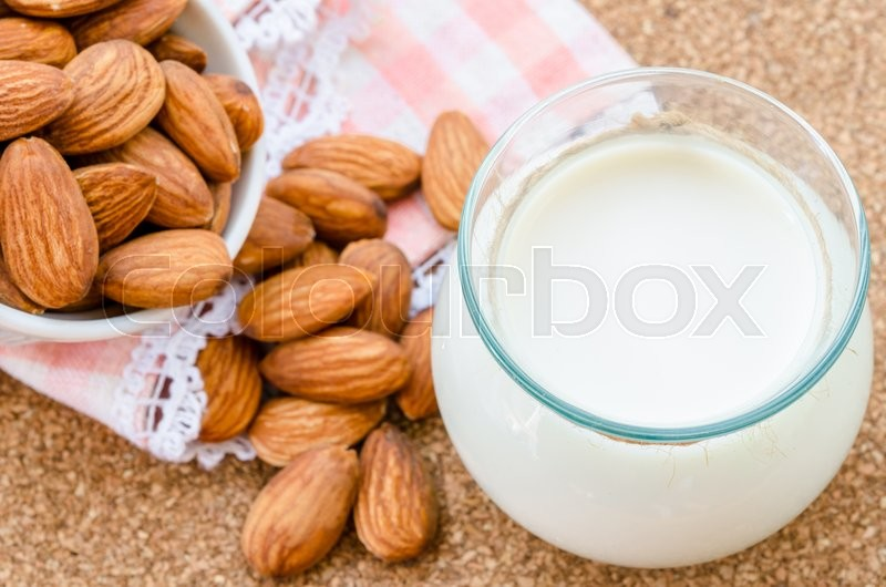 Almond milk in glass with almonds seeds on wood table, stock photo