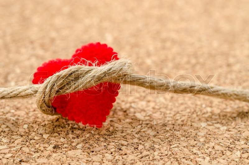 Stock image of 'Red heart with a bundle rope on wooden board'
