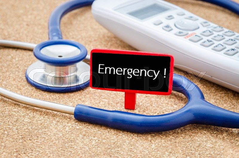Stock image of 'Phone and stethoscope on the table with EMERGENCY HOTLINE words on the board. Medical concept.'