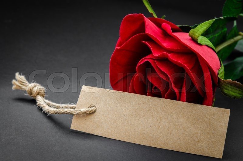Stock image of 'Black recycle brown paper tag with red rose on blackground.'