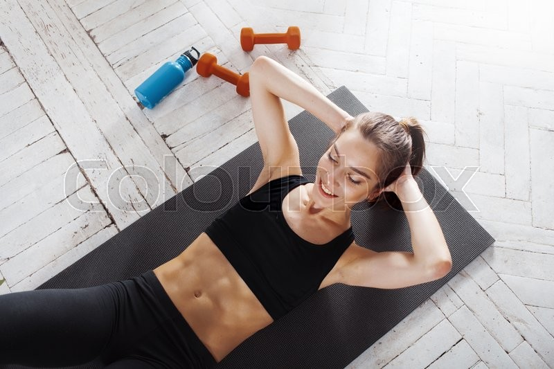 Stock image of 'Beautiful slim brunette  doing some push ups a the gym'
