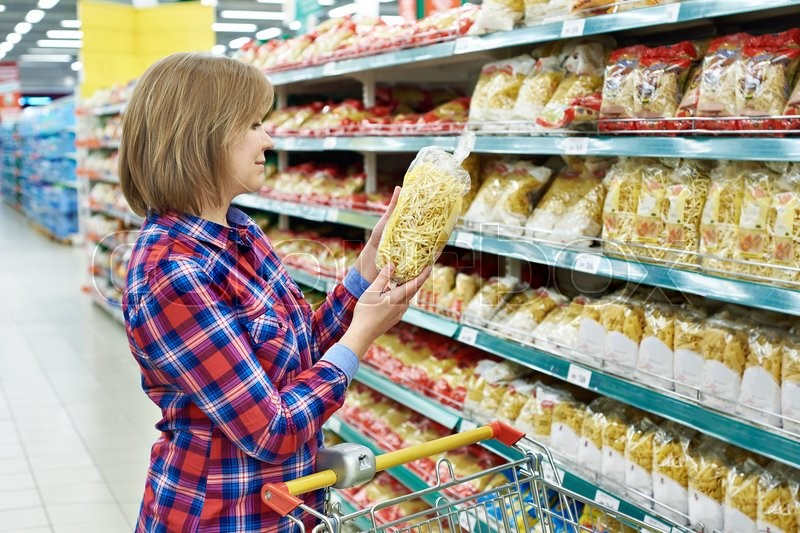 Stock image of 'Woman with a package pasta in the shop'