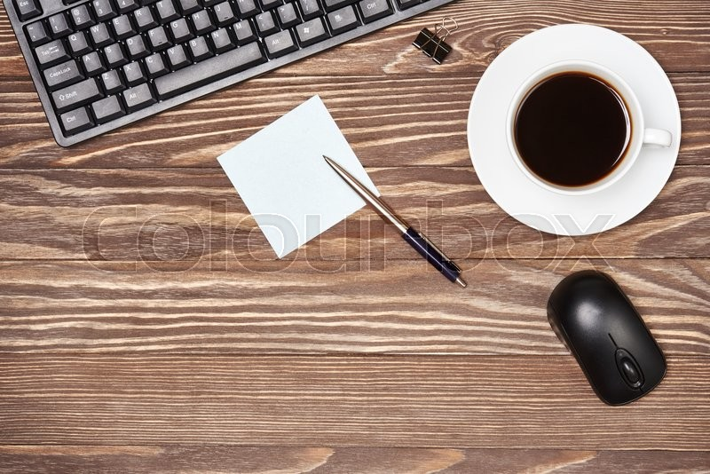 Stock image of 'Office desk table with keyboard and coffee cup on wooden background'