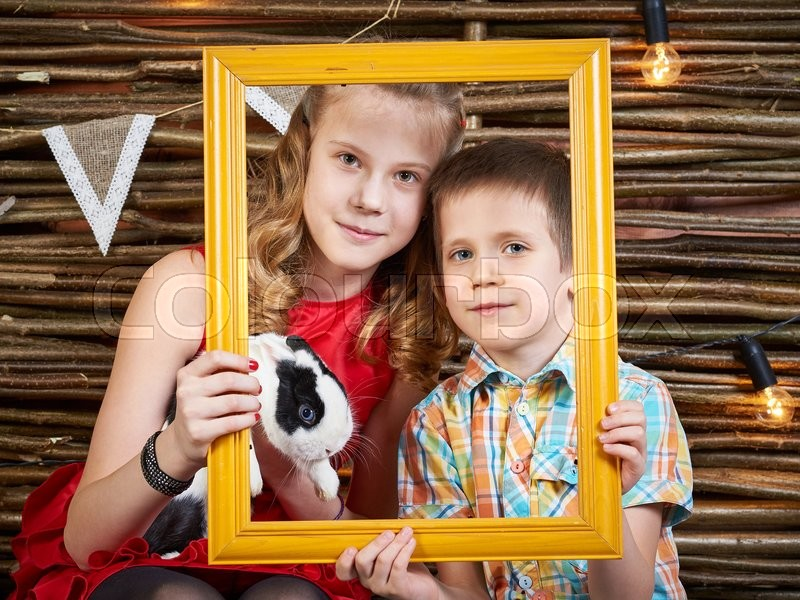 Stock image of 'Happy girl and boy with rabbit in frame of picture'