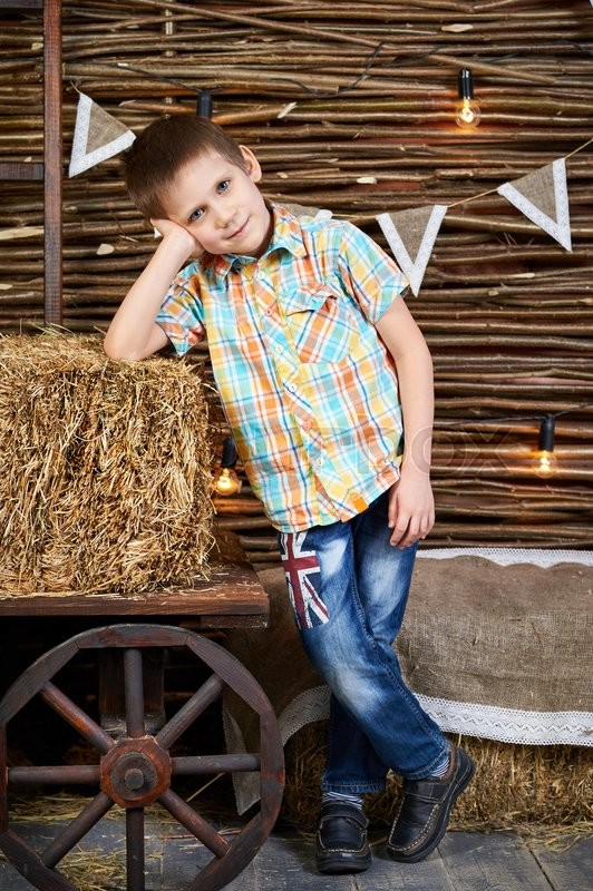 Stock image of 'Handsome boy is standing near ancient cart with hay rick in the studio'