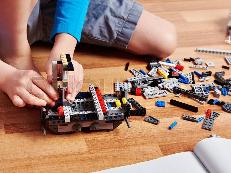 Stock image of 'Child collects plastic building kit on wooden floor'