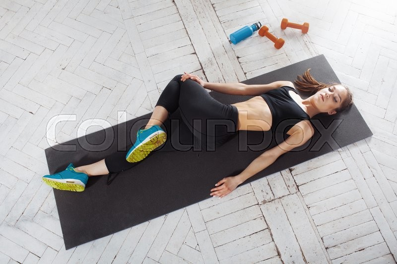 Stock image of 'Beautiful young slim woman  doing stretching exercises at the gym '