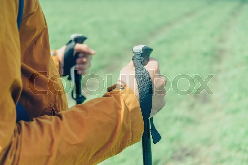 Stock image of 'Close-up image of male hands with trekking poles outdoor'