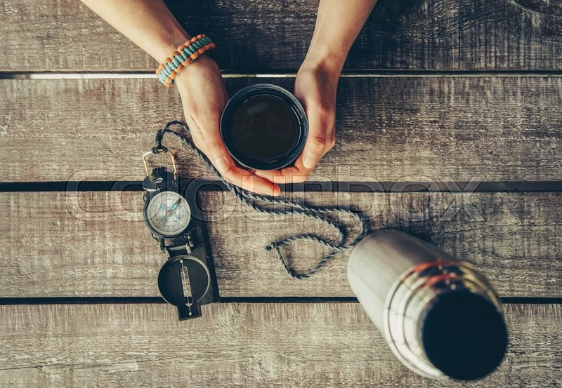 Stock image of 'Traveler woman holding a cup of tea on wooden table, point of view shot. Thermos and compass on wooden table. Toned image'