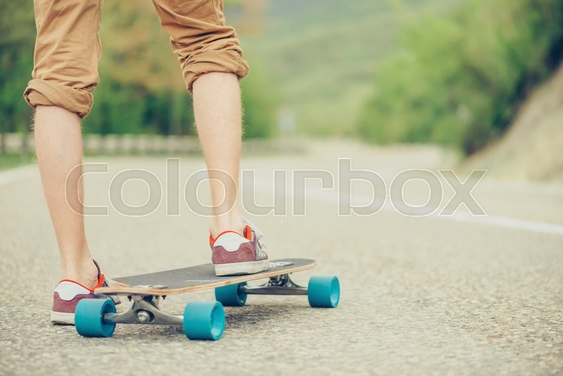 Stock image of 'Unrecognizable guy standing on longboard on road in summer, view of legs'