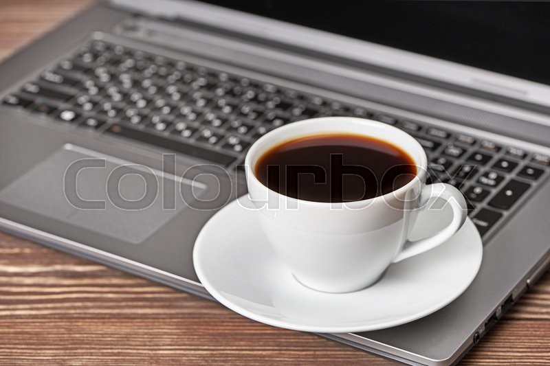 Stock image of 'Office desk table with laptop and coffee cup'
