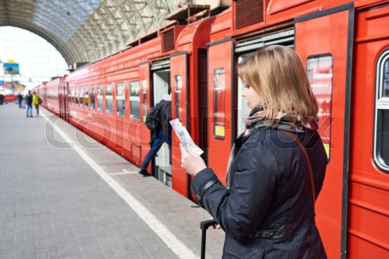 Stock image of 'Woman near the train checks his ticket to the station platform'