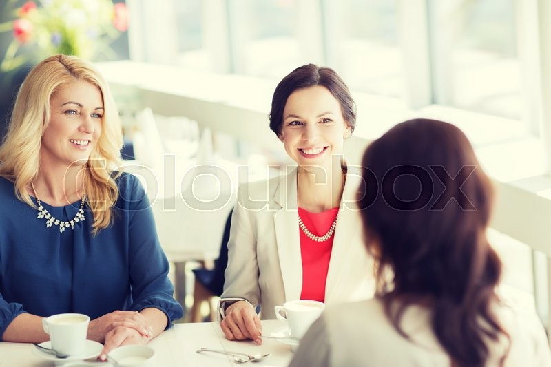 Stock image of 'people, communication and lifestyle concept - happy women drinking coffee and talking at restaurant'