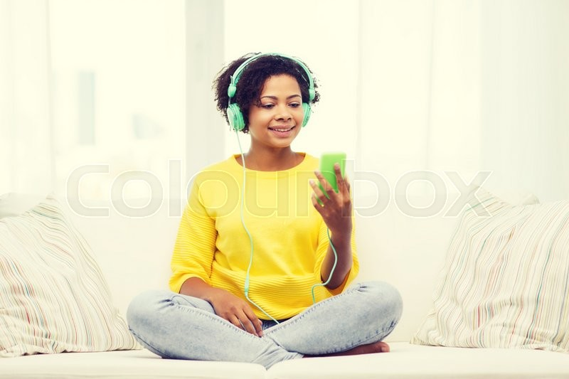 Stock image of 'people, technology and leisure concept - happy african american young woman sitting on sofa with smartphone and headphones listening to music at home'