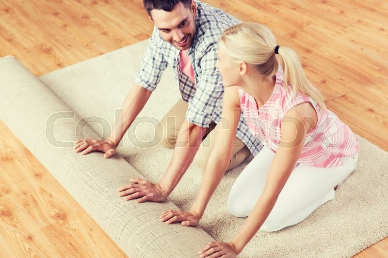 Stock image of 'people, repair and renovation concept - happy couple unrolling carpet or rug on floor at home'