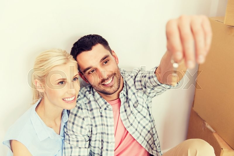Stock image of 'home, people and real estate concept - happy couple with key and cardboard boxes moving to new place'