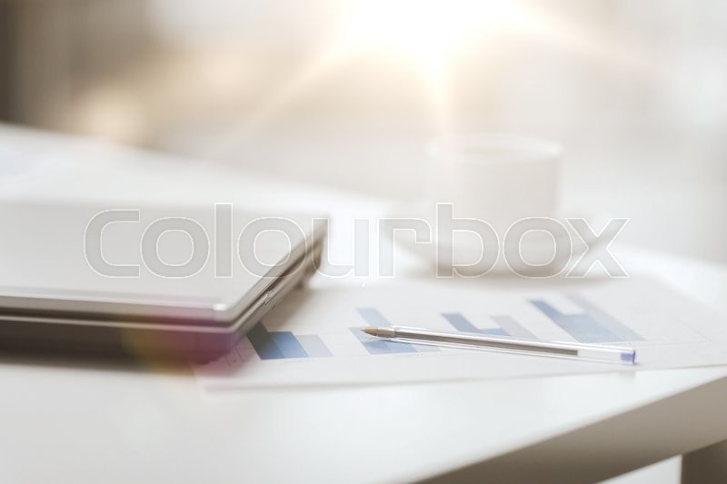 Stock image of 'business, technology and beverage concept - close up of laptop computer, charts, pen and coffee in office'