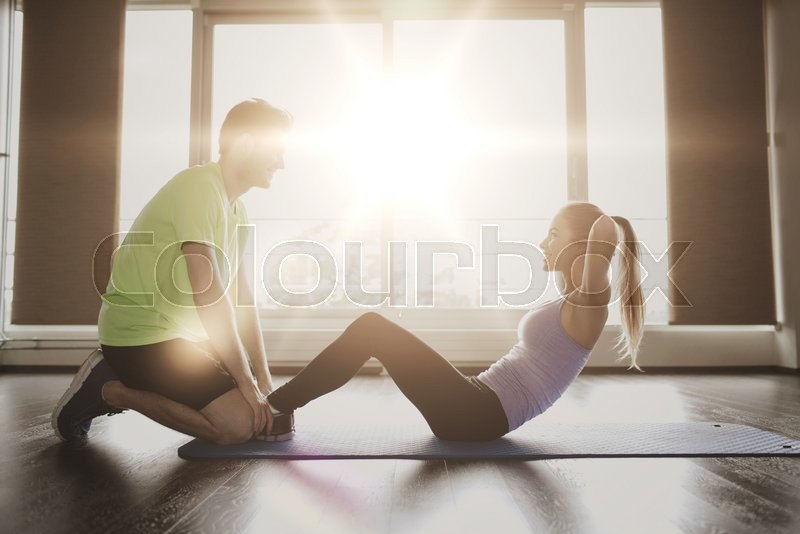 Stock image of 'fitness, sport, training, teamwork and people concept - woman with personal trainer doing sit ups in gym'