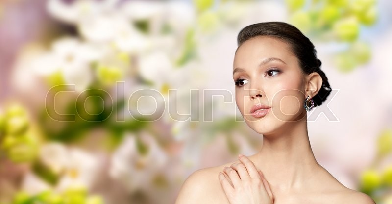 Stock image of 'beauty, jewelry, accessories, people and luxury concept - close up of beautiful asian woman face with earring over natural spring lilac blossom background'