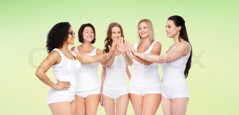 Stock image of 'gesture, friendship, beauty, body positive and people concept - group of happy different women in white underwear making high five over green natural background'