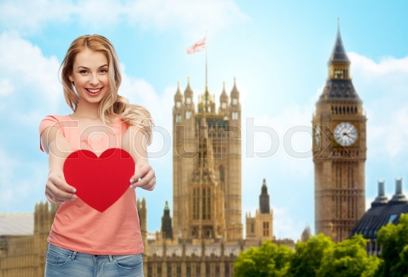 Stock image of 'love, travel, tourism, valentines day and people concept - smiling young woman or teenage girl with blank red heart shape over big ben london and city background'
