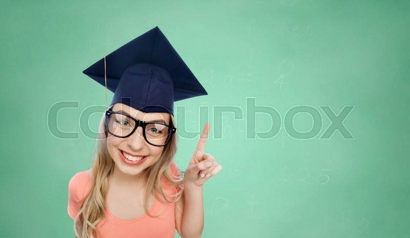 Stock image of 'people, graduation and education concept - smiling young student woman in mortarboard and eyeglasses pointing finger up over green school chalk board background'