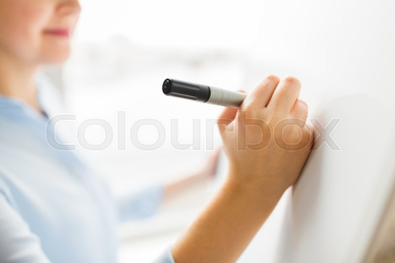 Stock image of 'office, business, people and education concept - close up of woman with marker writing or drawing something on white board'