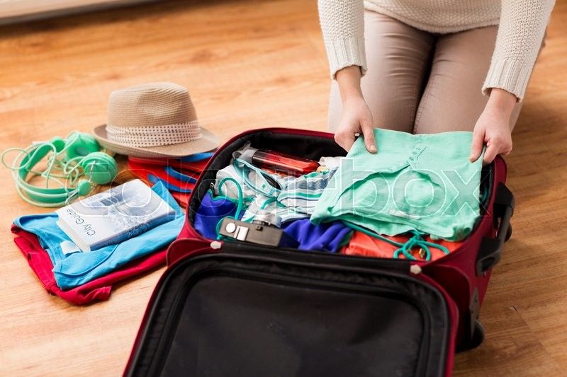 Summer vacation, travel, tourism and objects concept - close up of woman packing travel bag for vacation, stock photo