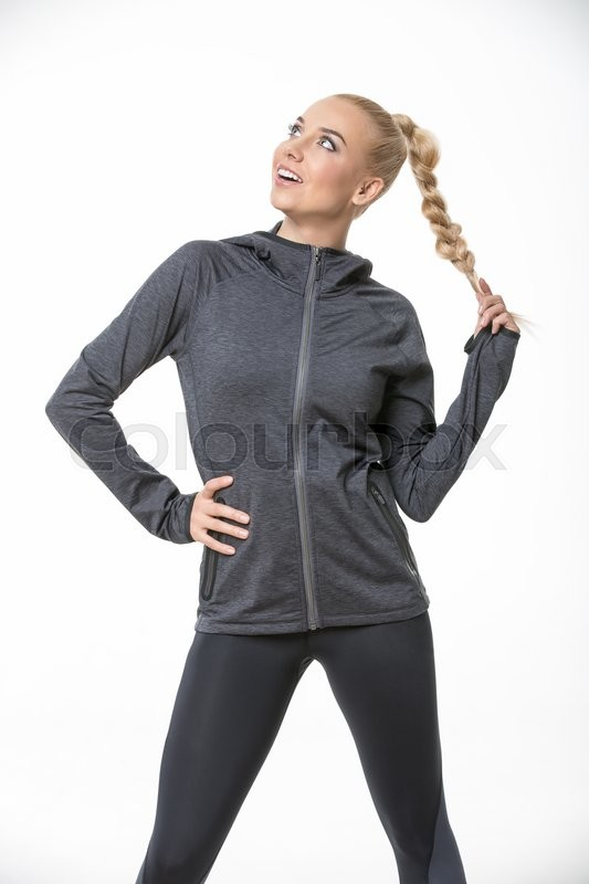 Stock image of 'Attractive blonde girl in the sportswear stands on the white background in the studio. She wears black-gray pants and gray hoody. She holds her right hand on her waist. She holds her plait with left hand. She looks to the right and up with a smile. Vertical.'