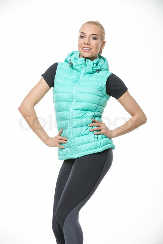 Stock image of 'Attractive blonde girl in the sportswear stands on the white background in the studio. She wears black-gray pants, black t-shirt and mint vest. She holds her hands on her waist. She has a plait on her head. She looks into the camera with a smile. Vertical.'