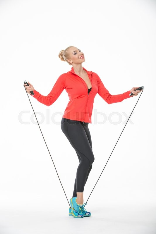 Stock image of 'Smiling blonde girl in the sportswear stands with skipping rope on the white background in the studio. She wears cyan-yellow sneakers, black pants, black t-shirt and red hoody. Her feet are on the skipping rope. She pulls up the skipping rope with her hands. Her right leg partially turned to the left with foot on the toe. She looks into the camera with a smile. Vertical. '