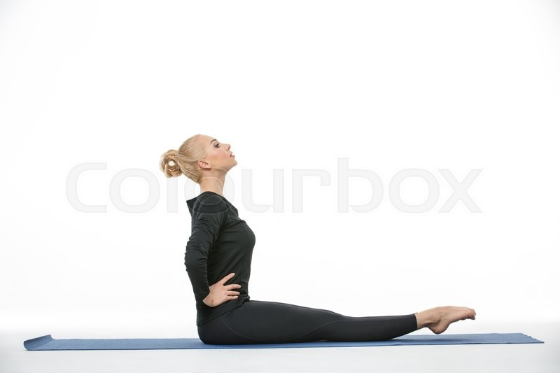 Stock image of 'Athletic blonde girl in the sportswear does exercise barefoot on the white background in the studio. She wears black pants and black long sleeve t-shirt. She sits on a blue gymnastic mat with hand on the waist. Her toes looks forward. She looks forward. Photographed from the side. Horizontal.'