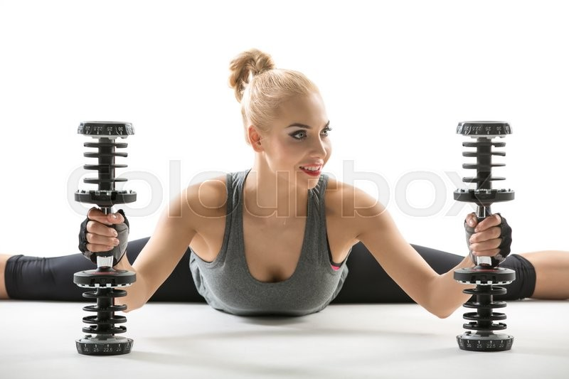 Stock image of 'Smiling blonde girl in the sportswear makes the splits on the white background in the studio. She wears black pants, gray sleeveless t-shirt and dark sports gloves. She holds the dumbbells while her torso tilted forward. She looks to the side with the slightly turned head. Horizontal.'