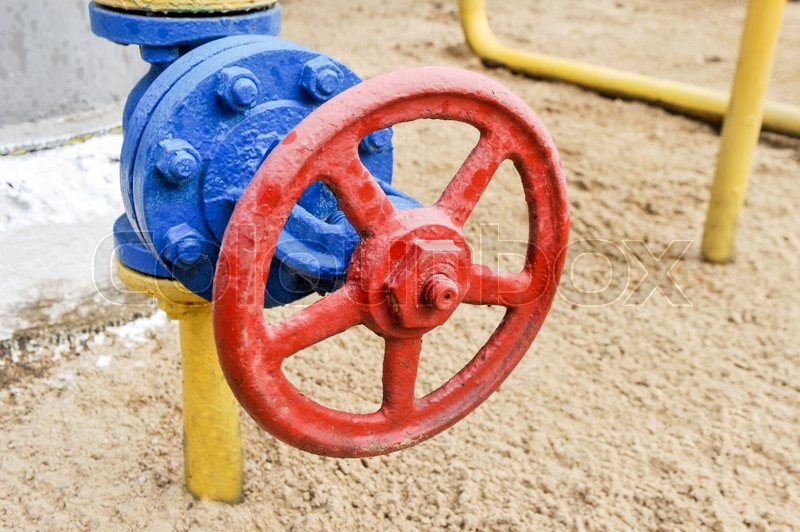 Stock image of 'Red faucet with steel pipe in natural gas compressor station in summer day'