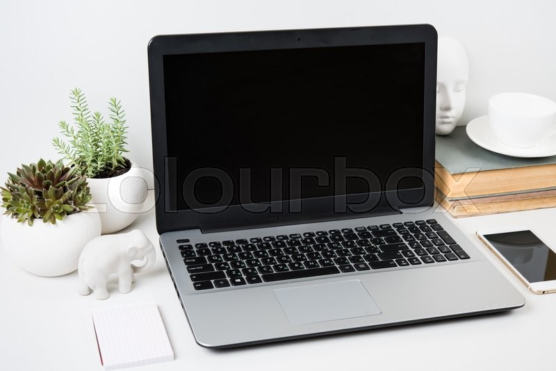 Stock image of 'Realistic modern work space with laptop mockup on a table on white background'