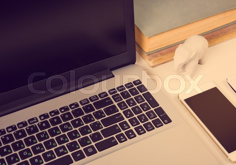 Stock image of 'Realistic modern work space with laptop and office objects on a table closeup'