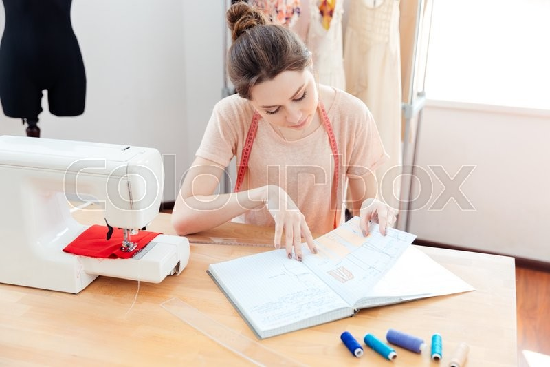 Stock image of 'Thoughtful woman seamstress working in studio'