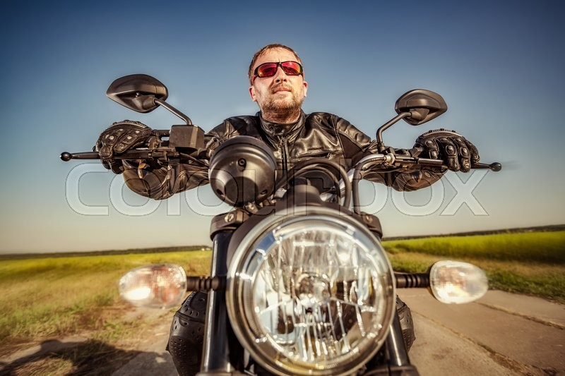 Biker in a leather jacket riding a motorcycle on the road. Filter applied in post-production, stock photo