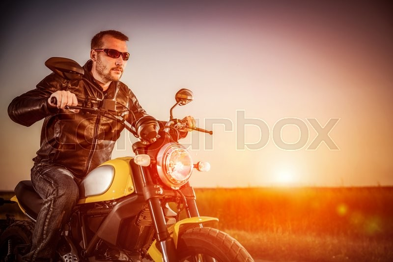Biker man wearing a leather jacket and sunglasses sitting on his motorcycle looking at the sunset, racing on the road. Filter applied in post-production, stock photo